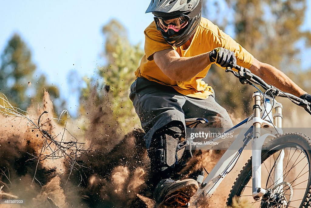 Close up of a mountain biker ripping through dirt.