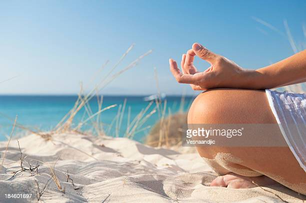 Close up of a person meditating on the sand at the beach