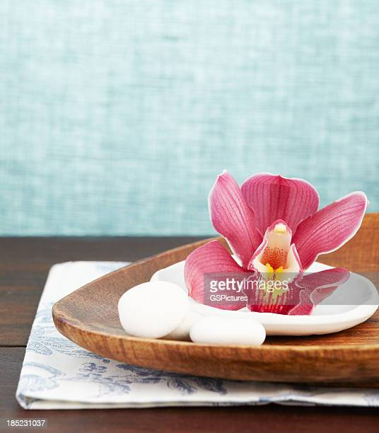 Close up of a pink orchid on wooden tray