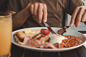 man eating an english breakfast with orange juice on a black table
