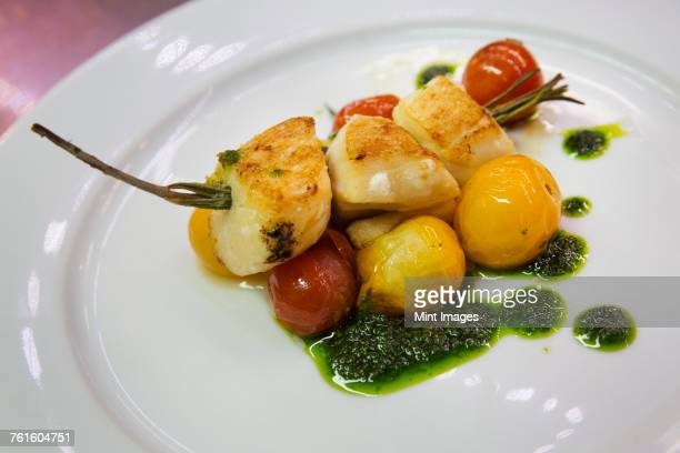Close up of a plate with grilled scallops, tomatoes and basil pesto.