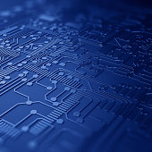 Close up of a printed blue computer circuit board with depth of field.