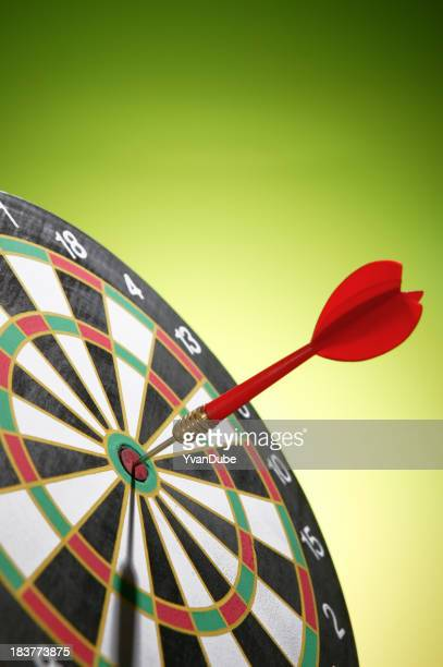 Close up of a red dart in the bullseye of a dart board