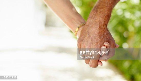 クローズアップの年配のカップル手をつなぐ