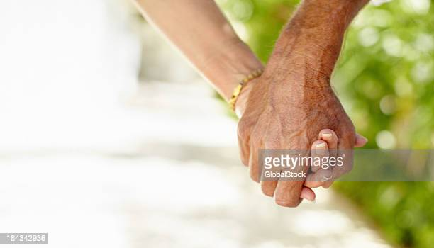 Close up of a senior couple holding hands