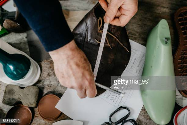 Close up of a shoemaker taking measurements for making a shoe