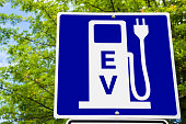 Close photo of a Blue Sign indicating an Electric Vehicle Recharging Point. Green Trees are Visible in Background. Ecological Mode of Transport.
