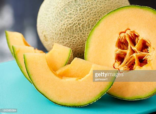 A close up of a sliced cantaloupe on a blue table