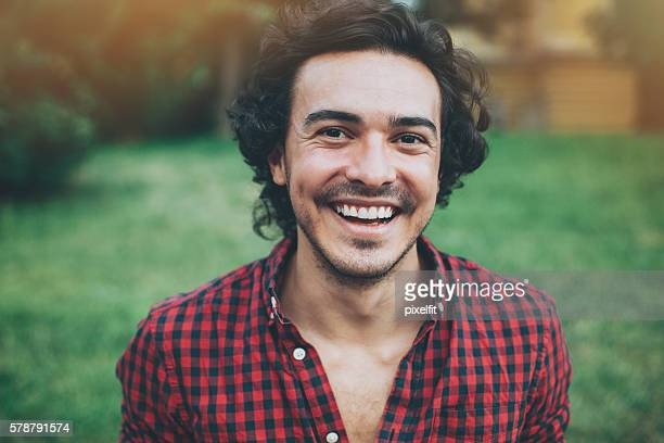Close up of a smiling young man in the park