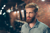 Close up of a stunning look of a red bearded guy with trendy hairdo in a barber shop. Looking so fashionable and confident