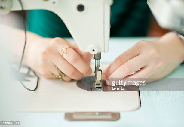Close up of a tailor using sewing machine