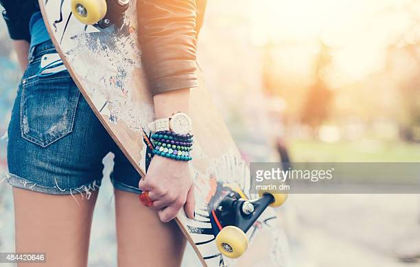Close up of a teenage girl holding skateboard