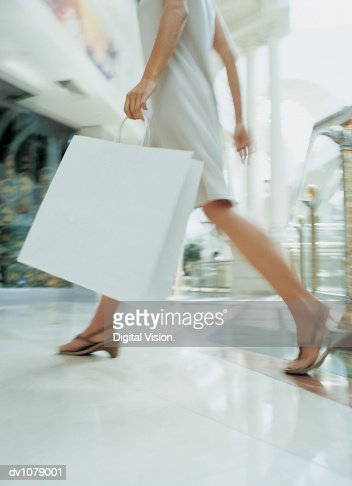 Close up of a the Legs of a Woman Walking Through a Shopping Mall Carrying a Shopping Bag : Stock Photo