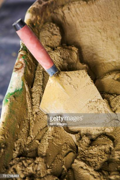 Close up of a trowel in a wheelbarrow full of cement.