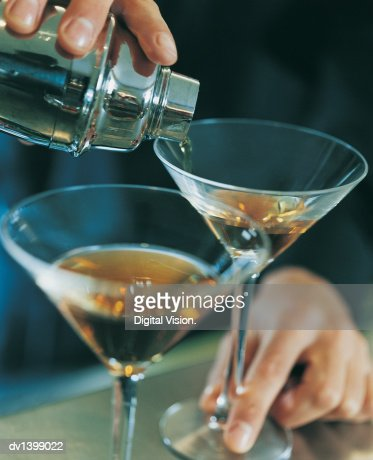 Close up of a Waiter Pouring Brandy into Cocktail Glasses : Stock Photo