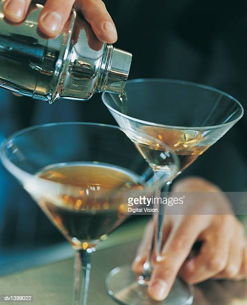 Close up of a Waiter Pouring Brandy into Cocktail Glasses