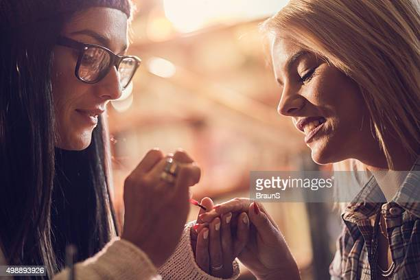 Close up of a woman painting her friend's nails.