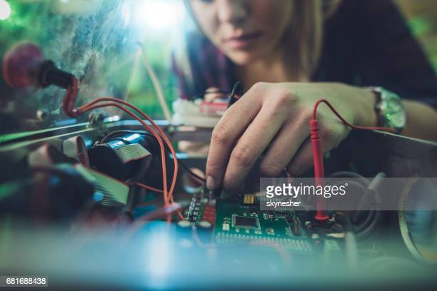 Close up of a woman repairing electrical component of a computer.