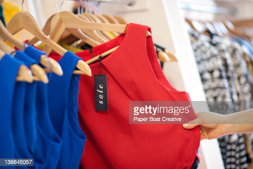 close up of a woman selecting a red dress on sale