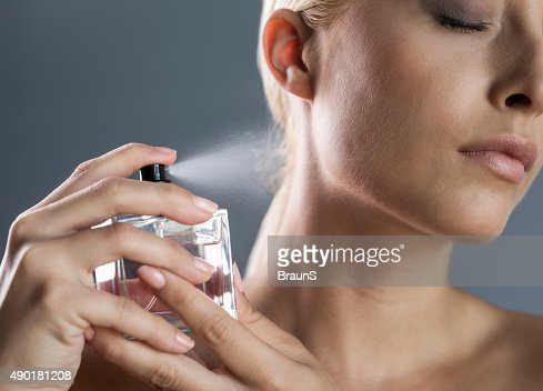 Close up of a woman spraying perfume on her neck.