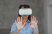 Close up of a woman having fun while using VR at home. Focus is on her hands.