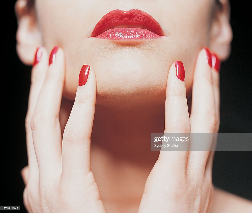 Close up of a Woman Wearing Red Nail Polish and Lipstick