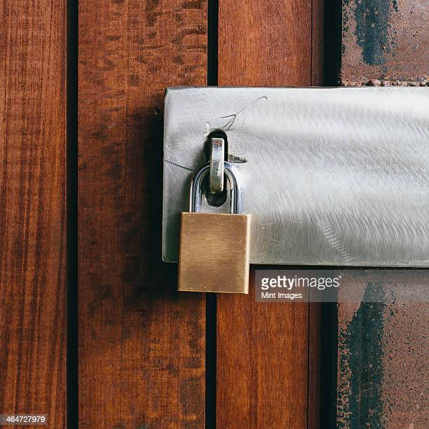 Close up of a wooden doorway, with a padlock.