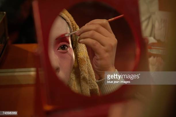 Close up of a young actress applying traditional Chinese face paint to her eyebrow in the mirror.
