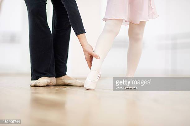 Close up of a young ballerina and teacher practicing toe point