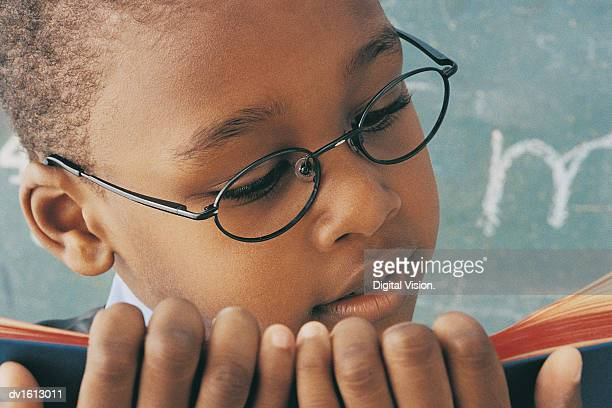 Close up of A Young Boy Wearing Spectacles Reading a Book