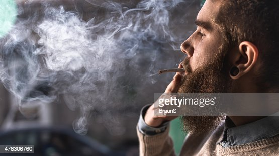 Close up of a young hipster smoking cigarette.