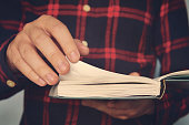Close up of a young male in a chequered shirt holding the book and turning over the page. Ingusitive man reads the book on the run. Person is standing and reading. Cursory reading. Leafing over pages