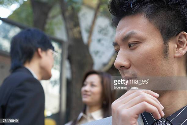 Close up of a young man listening to another young man and young woman talk outside a restaurant.
