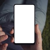 Close up of a young man sitting long holding smartphone with the white screen. Person is on-line from a smartphone. Close up of a man use of the cellphone. Blank screen for graphics display montage