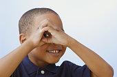 Close up of African American boy peeking through hands