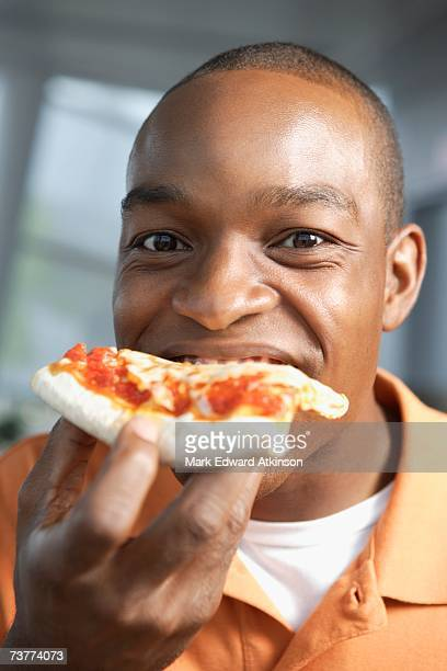 Close up of African man eating pizza