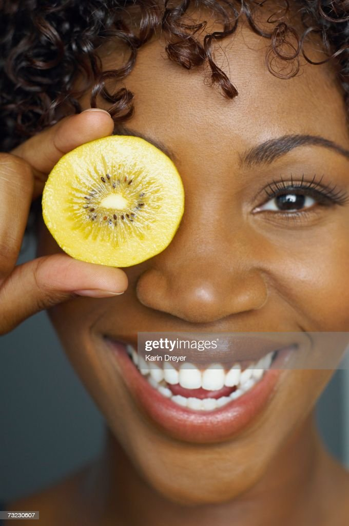 Close up of African woman holding slice of fruit in front of eye