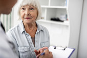 Calm elderly lady standing close to her doctor and looking attentively at him
