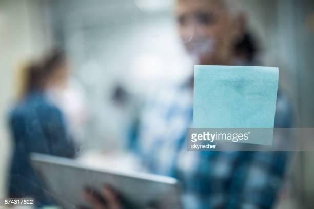 Nahaufnahme von einer leeren Klebstoff Hinweis auf eine Glaswand. Kopieren Sie Raum.