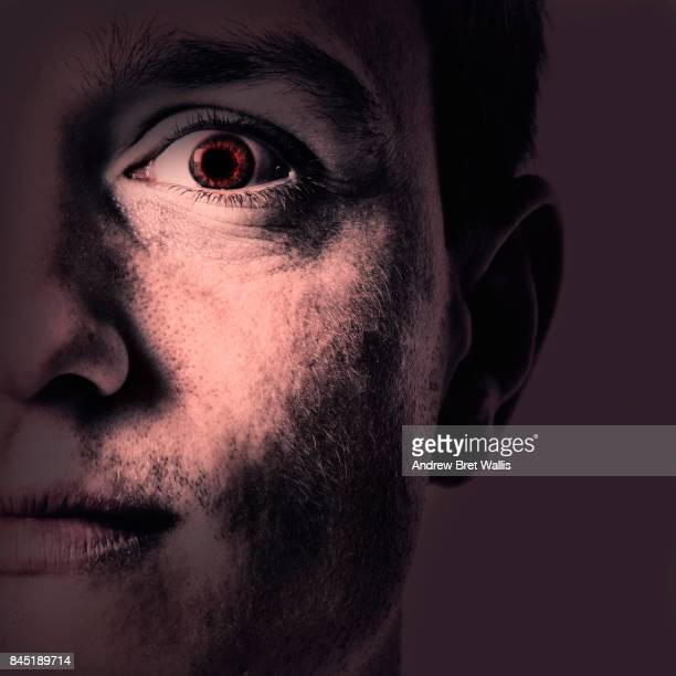 Close up of an evil male face appearing out of darkness