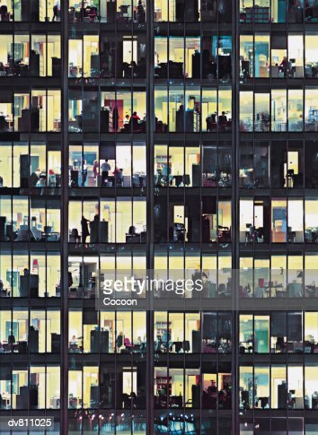 Close up of An office Building at Night With Business Executives Working Late : Stock Photo