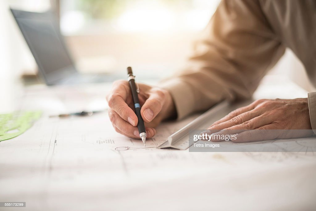 Close up of architects hands drawing on blueprint