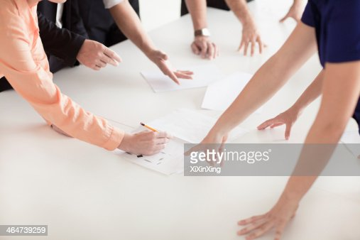 Close up of arms and hands of business people in the office having a business meeting