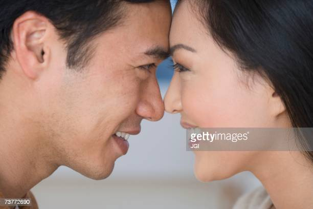 Close up of Asian couple touching foreheads