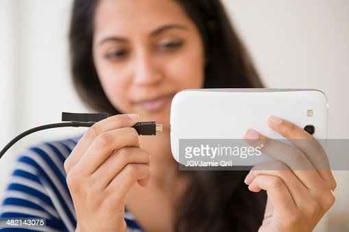 Close up of Asian woman connecting cell phone to battery : Stock Photo