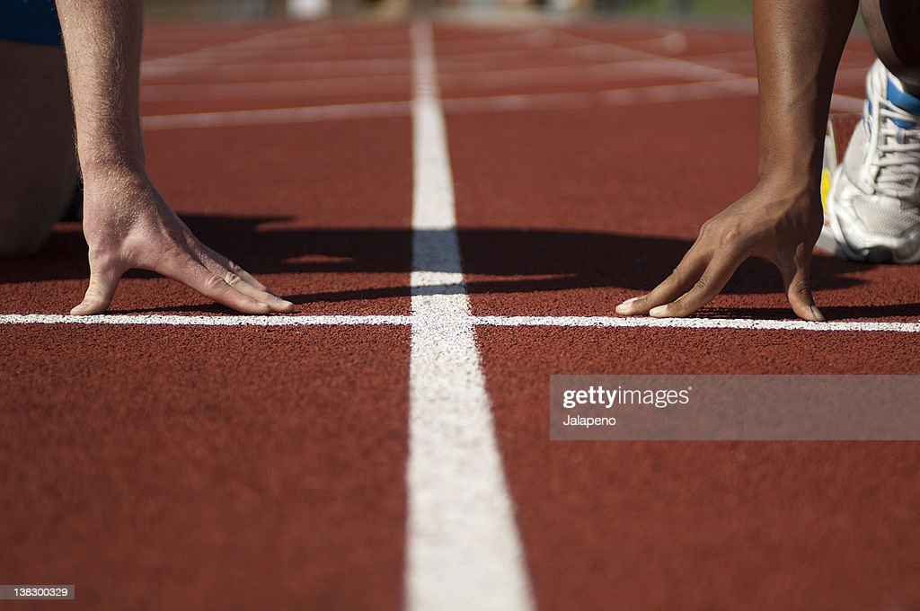 Close up of athletes' hands on track : Stock Photo