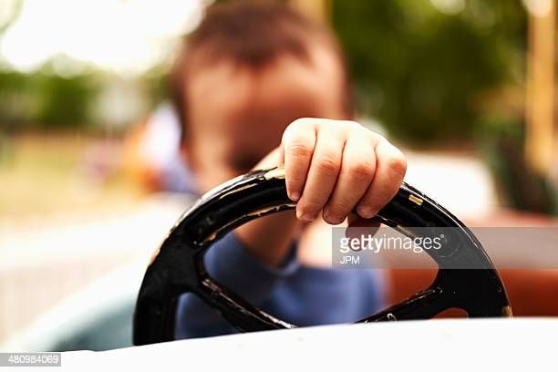 Close up of baby boy driving toy car