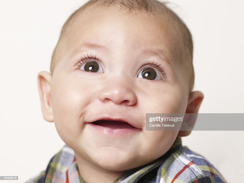 Close up of baby boy (5 months) smiling, studio shot, close-up : Stock Photo