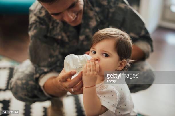 Close up of baby girl drinking water with her father's help