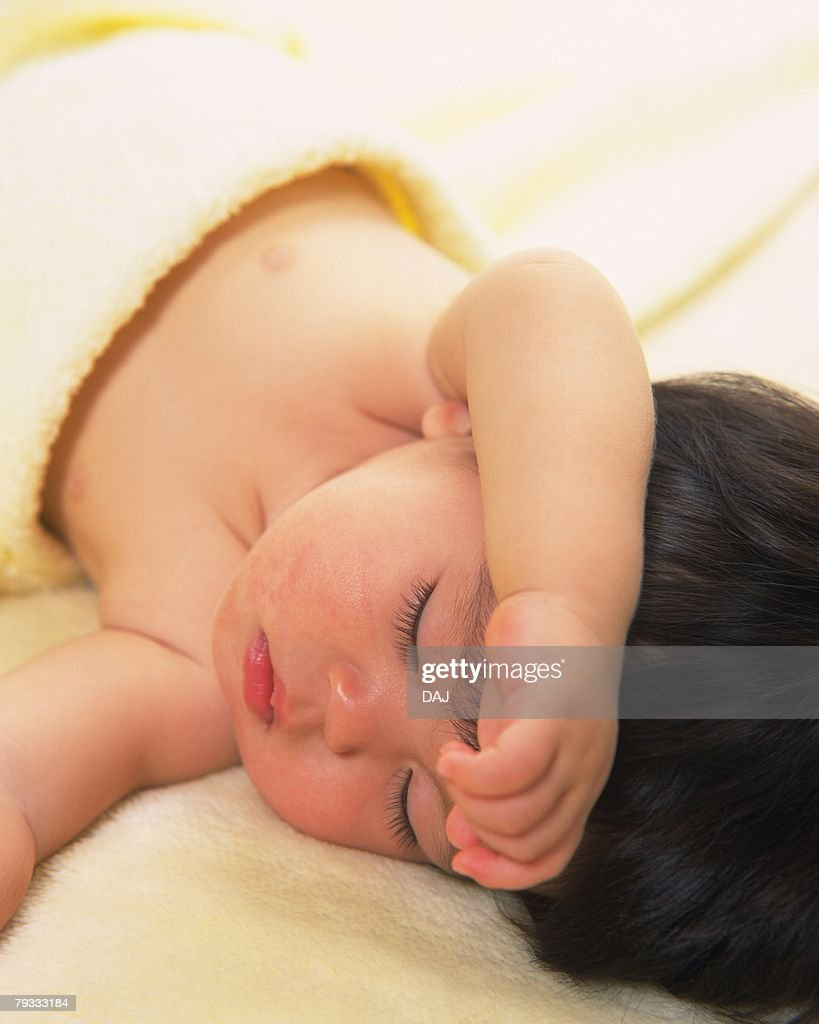 Close up of baby girl sleeping in yellow blanket, portrait, Full Frame : Stock Photo